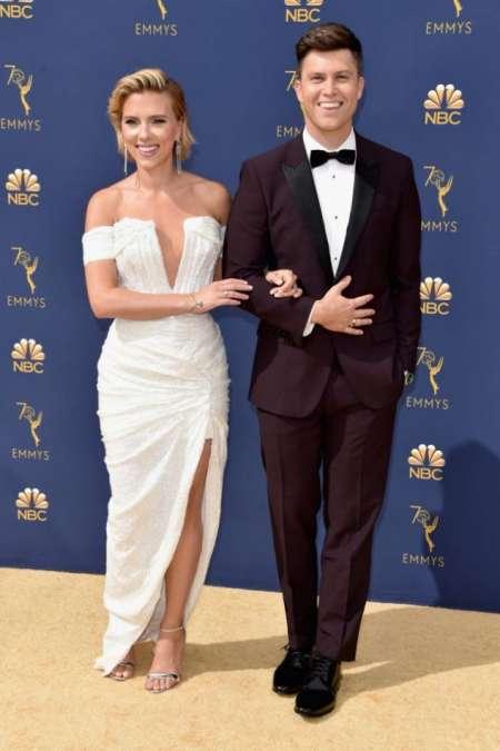 Colin Jost, presentador de la gala, sonriente junto a su pareja Scarlett Johansson (Balmain)